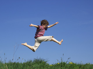 child-leaping-through-meadow